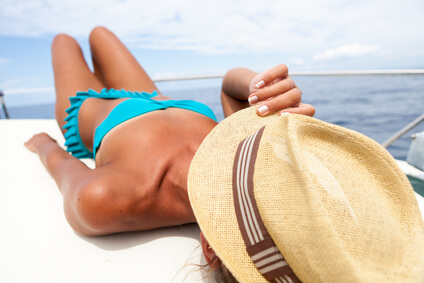 Attractive girl sunbathing on a yacht holding her hat